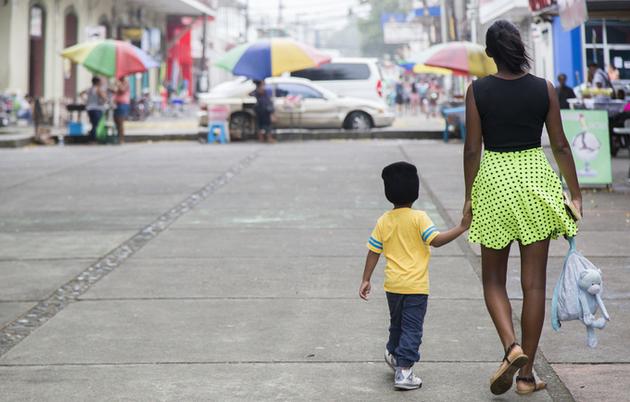 Una joven camina con su hijo, nacido de un embarazo adolescente, por un bulevar de una urbe de América Latina, donde ese tema de salud y vida representa un multimillonario costo de oportunidad para sus sociedades. Foto: UNFPA