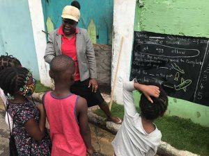 Un grupo de escolares recibe clases de una maestra en una comunidad de bajos recursos de Kingston, la capital de Jamaica. Para ello, la docente improvisó pizarrones en las paredes para que sus alumnos sigan instruyéndose pese al cierre de las escuelas por la pandemia de covid. Foto: Kate Chappell