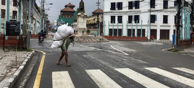 Un trabajador pobre carga un fardo en una calle de Katmandú, la capital de Nepal. Millones de familias trabajadoras pueden caer en la pobreza o salir de ella según las políticas que adopte el mundo al paso de la actual pandemia, según la Unctad y el PNUD. Foto: Vibhu Mishra/ONU