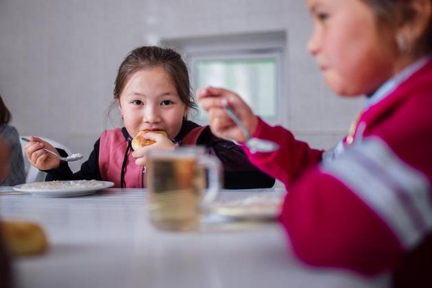 Nurel, de siete años, come un almuerzo saludable preparado por un cocinero en su escuela de Chon Kenin, Kirguistán. Millones de niños han perdido el último año el beneficio de la alimentación escolar. Foto: Zhanibekov/Unicef