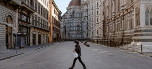 Una solitaria transeunte cruza junto a la turística Plaza del Duomo, en la ciudad italiana de Florencia, vacía por las medidas contra el coronavirus. La industria del turismo se desplomó en 2020 y su recuperación puede demorar varios años. Foto: Francesco Spighi/Unicef