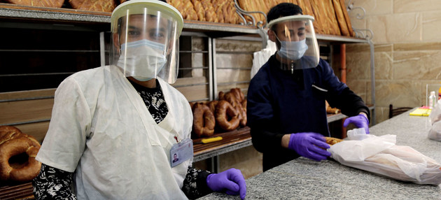 Vendedores en una panadería de Constantine, en Argelia, durante la pandemia. En todo el mundo se perdieron 8,8 por ciento de las horas de labor, y el sector de hotelería y restauración fue el más afectado, según la OIT. Foto: Yacine Imadalou/OIT