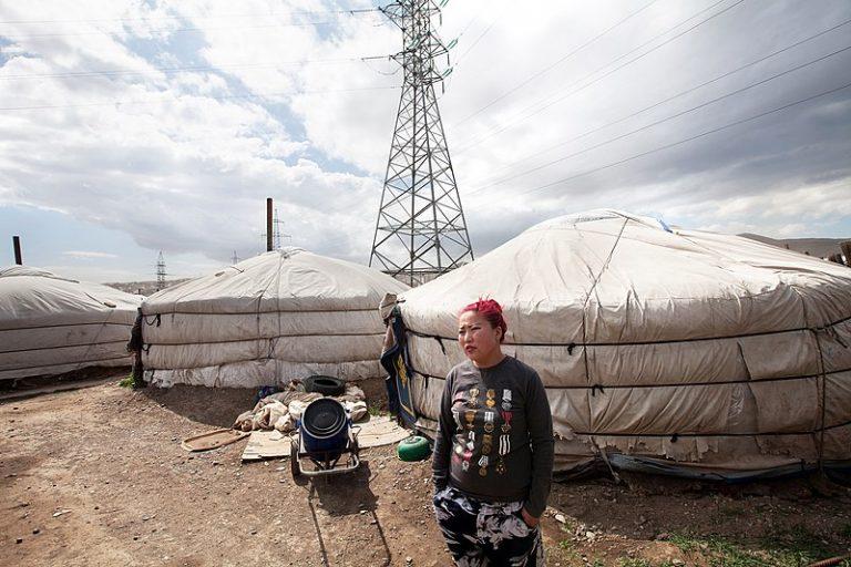 Una mujer fuera de un grupo de yurtas (viviendas móviles de los nómadas) en el distrito de Ger, cerca de la capital mongola, Ulaanbaatar, al lado de la red eléctrica. El gobierno de Mongolia está tomando medidas aceleradas para que en el país domine la energía limpia y que en 2050 se alcance la meta de emisiones netas cero de gases contaminantes. Foto: Nathalie Daoust/ CC BY-SA 4.0