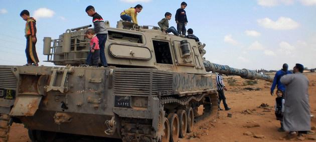 Niños juegan sobre un tanque destruido en medio de la guerra civil que duró años en Libia y produjo numerosas violaciones a los derechos humanos por milicias cuyos jefes ahora se integran a estructuras de gobierno. Foto: Maximilian Dyck/Unimas
