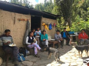 Maribel Palomino, con suéter verde, sentada en el quicio de la puerta de la casa de sus padres, rodeada de su familia. Ella y sus dos hermanos retornaron a la casa familiar tras la pandemia, porque allí podían producir sus alimentos y cuidar que sus padres no se contagiasen de covid. En la finca familiar, en la comunidad de Muñapata, a 3158 metros de altura, en la región peruana de Cusco, Palomino cultiva ahora un biohuerto, que le garantizan los ingresos necesarios para mantenerse ella y su hijo. Foto: Cortesía de Maribel Palomino