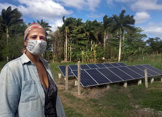 La productora Kety Díaz delante de los paneles solares que instaló en su finca La Cotorra, gracias al Proyecto de Sostenibilidad Alimentaria para Municipios (Prosam), un programa que funciona en Cuba con respaldo de la cooperación internacional. La finca, situada en el municipio de Guanabacoa, en la periferia de La Habana, forma parte de la Cooperativa de Crédito y Servicio José Martí. Foto: Patricia Grogg / IPS