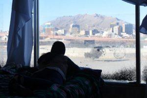Una joven mira hacia uno de los pasos fronterizos entre México y Estados Unidos desde un albergue en Ciudad Juárez, en enero de este año. Foto: Rey Jáuregui / Pie de Página