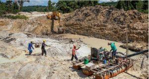 Una excavadora remueve la tierra mientras mineros reparan una bomba para trabajar con chorros de agua en el río Rato, afluente del Tapajós, estado de Pará, en la Amazonia brasileña. Foto: Lalo de Almeida/Raisg