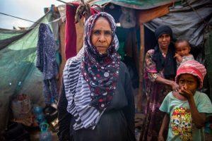 Una mujer yemení desplazada fuera de unas tiendas precarias, que comparte con su familia, en un campamento improvisado. Foto: OIM