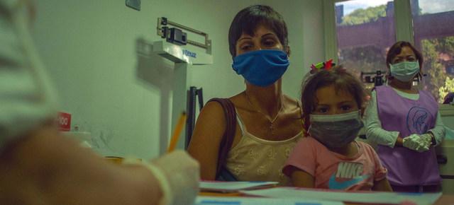 Una madre lleva a su hija a consulta en un centro de Venezuela. La OMS señala que, entre la escasez de recursos y el peso de la covid 19, servicios esenciales de salud sufren interrupciones en 90 por ciento de los países. Foto: Alejandra Pocaterra/Unicef