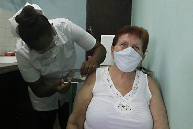 Carmen Puentes recibe la primera dosis del candidato de vacuna Abdala contra la covid-19 en un consultorio del policlínico Betancourt Neninger, en La Habana del Este. En 14 días esta ciudadana cubana de 70 años recibirá otras dos dosis en lapsos de 14 días entre ellas, como parte del esquema de inmunización establecido. Foto: Jorge Luis Baños/IPS