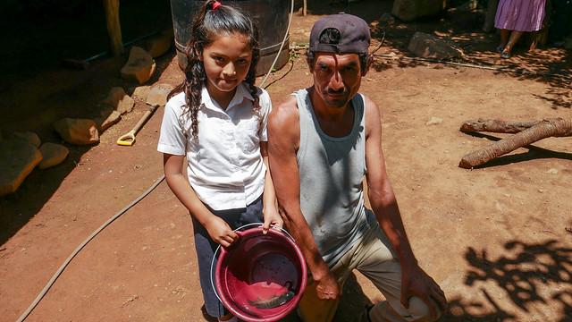 Cristino Martínez y una de sus hijas muestran la tilapia que acaban de pescar en el estanque familiar que han construido en el patio de su casa, en el caserío El Guarumal, en el oriental departamento de Morazán, en El Salvador. Esta numerosa familia campesina cría los peces para el autoconsumo y no para comercializarlos. Foto: Edgardo Ayala / IPS