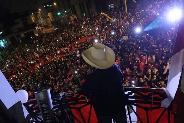 """Pedro Castillo, de espaldas y con su característico sombrero de paja, saluda a sus adeptos tras confirmarse que obtuvo la mayoría de los votos en las elecciones presidenciales en Perú, aunque su proclamación oficial está a la espera de aclarar los reclamos interpuestos por su contrincante, Keiko Fujimori. Grupos procedentes de la sierra y la selva, han llegado a Lima para """"defender"""" el triunfo del campesino, maestro y sindicalista de izquierda. Foto: Perú Libre /Twitter"""