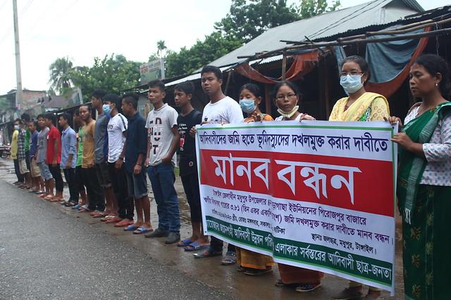Miembros de los pueblos indígenas de Bangladesh forman una cadena humana en el distrito de Tangail, en una de sus muchas iniciativas para exigir que se le reconozcan  derechos legales sobre sus tierras ancestrales, en especial en la jungla de Madhupur. Foto: Rafiqul Islam / IPS