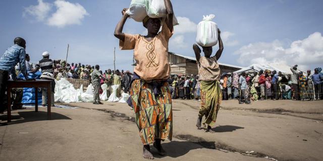 Mujeres cargan bultos con alimentos, producto de la cooperación internacional, en la ciudad de Bunia, oriente de la República Democrática del Congo. La pandemia covid-19, sumada a los conflictos y a la crisis climática, empuja a 47 millones de mujeres más hacia la pobreza extrema. Foto: John Wessels/Oxfam