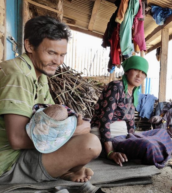 Chiring Tamang sostiene al nuevo bebé de la familia mientras su esposa Priya los observa.  Ella dio a luz a la niña en su casa,  en su aldea en el distrito de Sindhupalchowk,  en Nepal, en febrero de 2021. Foto: Marty Logan / IPS