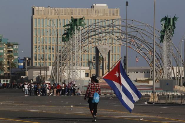 Una mujer porta una bandera de Cuba ante la sede de la embajada de Estados Unidos en La Habana, durante un acto en apoyo a la revolución. La Casa Blanca estudia aumentar el personal en su delegación, que quedó prácticamente vacía tras el cierre de los servicios consulares en 2017. Foto: Jorge Luis Baños / IPS
